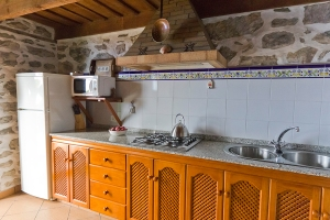 Spacious kitchen area with 4-ring gas hob, full size fridge/freezer and twin sinks